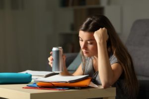 person studying and drinking an energy drink