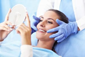 woman admiring her new smile after getting cosmetic dentistry