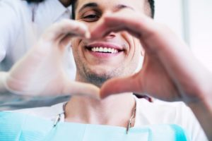 A smiling man and his dentist make a heart shape with their hands