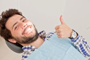 man dental chair smiling thumb up