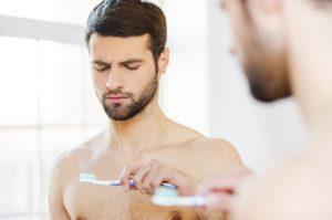 Man staring at toothbrush