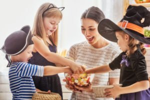 Kids in costume reaching into Halloween candy bowl